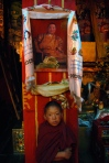 A boy monk in the holy city of Litang, China, posses with a portrait of the Dalai Lama in the city's main temple, in July 2010. (Photo by Juliana Jiménez Jaramillo).