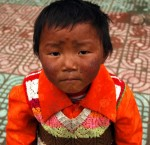 A Tibetan child is curious about the camera. He accompanies his father to the local bus station in Litang, China, one of the holiest Tibetan cities in the country. July 2010. (Photo by Juliana Jiménez Jaramillo.)